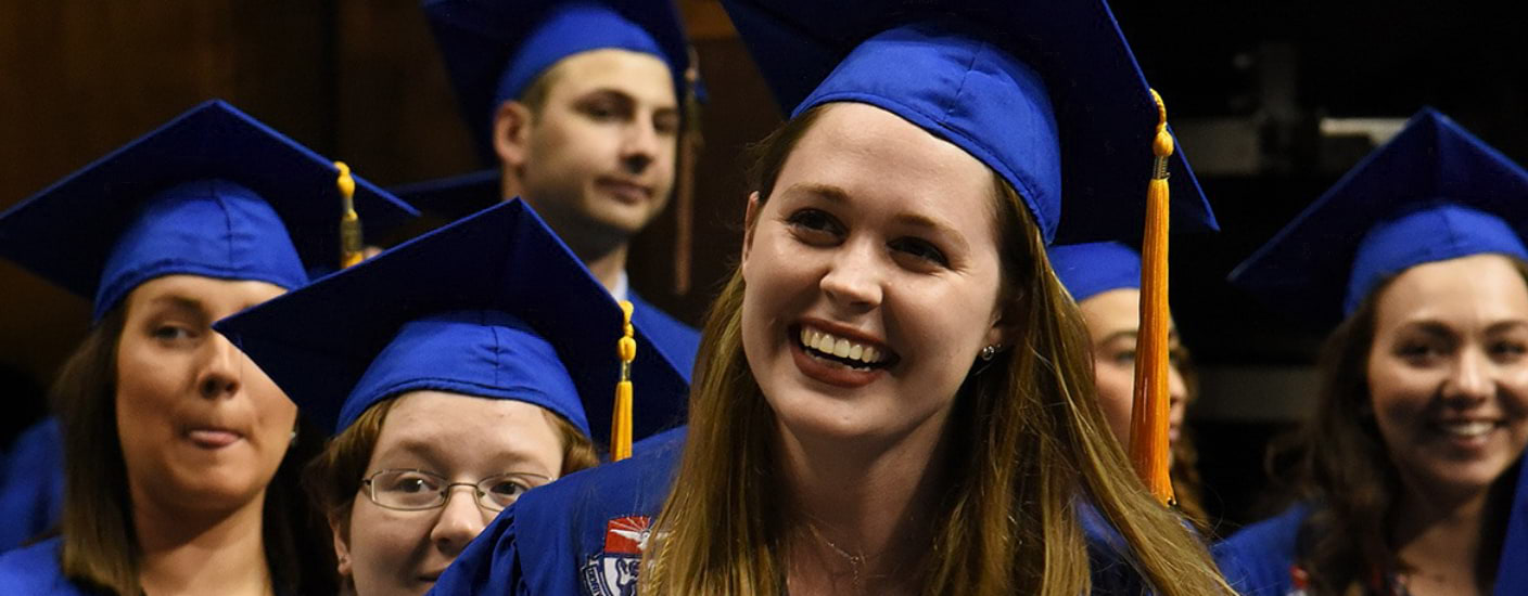 A picture of an graduate student smiling at graduation
