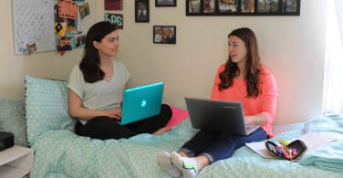 2 girls in a campus Dorm room conversating